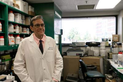 A photo of chemistry professor Mark Lovell in a lab coat in his lab.